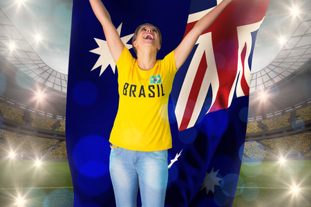Excited football fan in brasil tshirt holding australia flag against large football stadium with lights photo