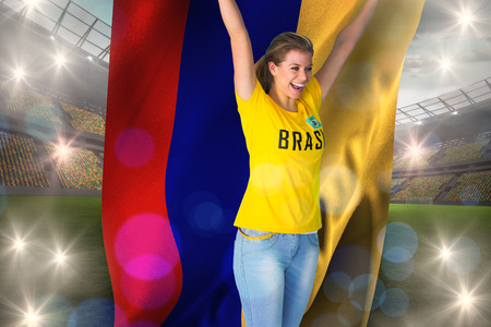 Excited football fan in brasil tshirt holding colombia flag against large football stadium with lights photo