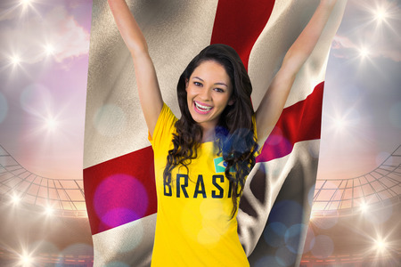 Excited football fan in brasil tshirt against holding england flag large football stadium under bright blue sky photo