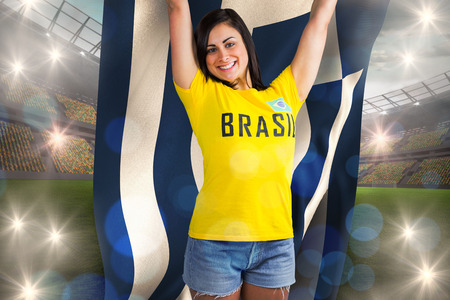 Excited football fan in brasil tshirt holding greece flag against large football stadium with lights photo