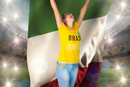 Excited football fan in brasil tshirt holding italy flag against large football stadium with lights photo