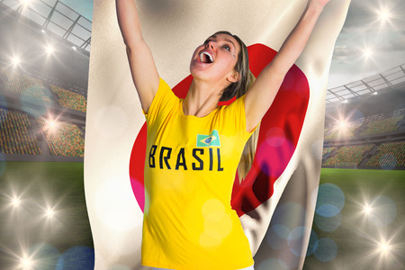 Pretty football fan in brasil t-shirt holding japan flag against large football stadium with lights photo