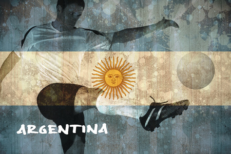 Football player in white kicking against argentina flag in grunge effect photo
