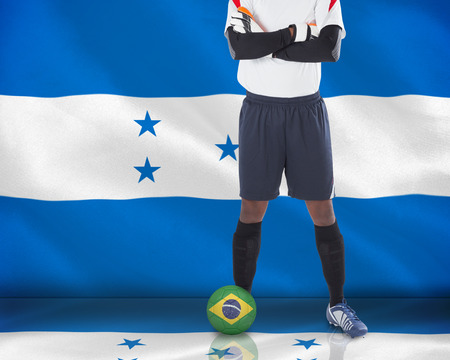 Composite image of goalkeeper in white with ball against digitally generated honduras national flag photo