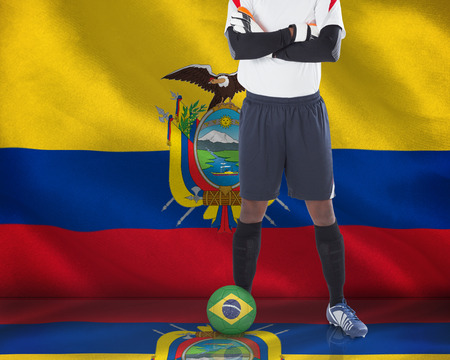 Composite image of football player standing with ball against digitally generated ecuador national flag photo