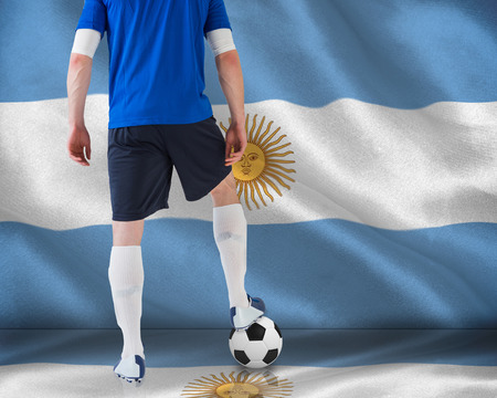 argentinian flag: Composite image of football player standing with ball against argentinian flag Stock Photo
