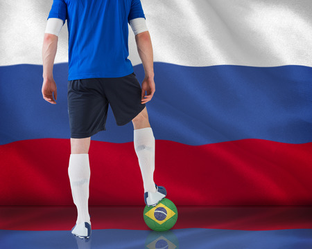 Composite image of football player standing with ball against digitally generated russian national flag photo