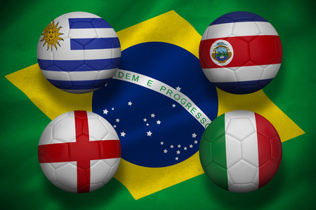Composite image of group d footballs for world cup against digitally generated brazilian national flag photo