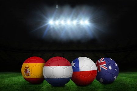 Composite image of footballs in group b colours for world cup against football pitch under spotlights photo