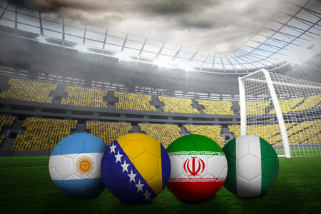 Composite image of footballs in group f colours for world cup against large football stadium with lights photo