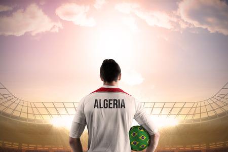 Algeria football player holding ball against large football stadium under bright blue sky photo