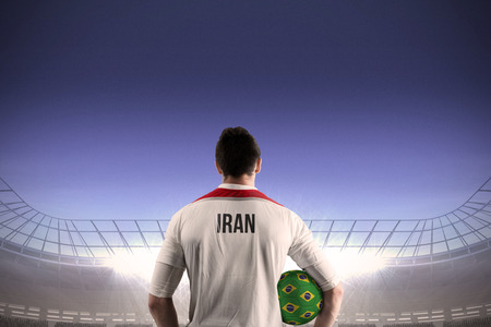 Iran football player holding ball against large football stadium under blue sky photo