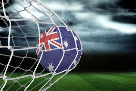 Football in australia colours at back of net against football pitch under stormy sky photo