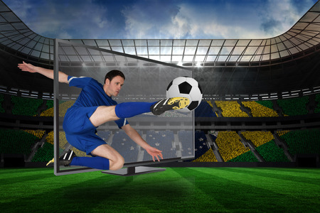 Composite image of football player kicking ball through tv against large football stadium with brasilian fans photo