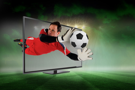 flat screen tv: Composite image of fit goal keeper saving goal through tv against football pitch under green sky and spotlights