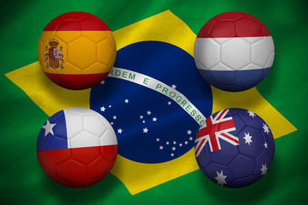 Composite image of group b footballs for world cup against digitally generated brazilian national flag photo
