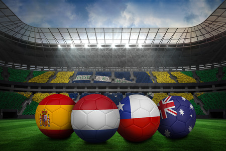 Composite image of footballs in group b colours for world cup against large football stadium with brasilian fans photo