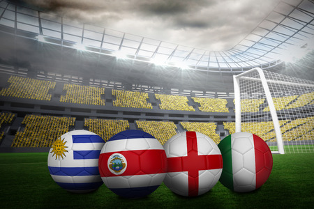 Composite image of footballs in group d colours for world cup against large football stadium with lights photo