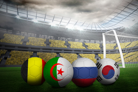 Composite image of footballs in group h colours for world cup against large football stadium with lights photo