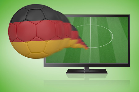 Football in germany colours flying out of tv against green vignette photo