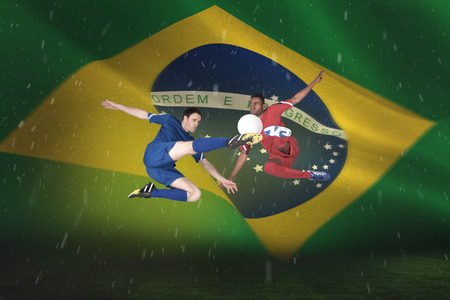 Football players tackling for the ball against brazilian flag waving photo