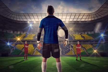 Composite image of goalie facing opposition against large football stadium with brasilian fans photo