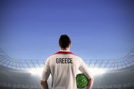 Greece football player holding ball against large football stadium under bright blue sky photo