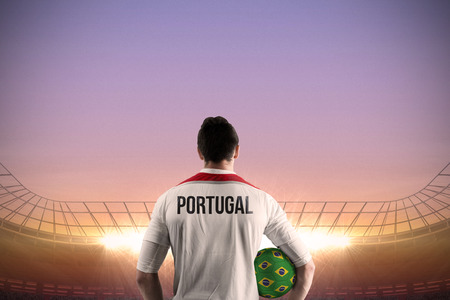 Portugal football player holding ball against large football stadium under purple sky photo