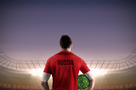 Russia football player holding ball against large football stadium under blue sky photo