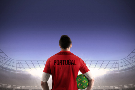 Portugal football player holding ball against large football stadium under blue sky photo