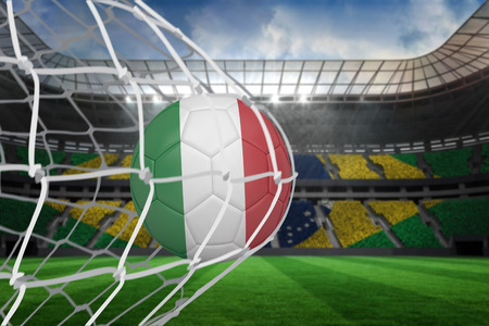Football in italy colours at back of net against large football stadium with brasilian fans photo