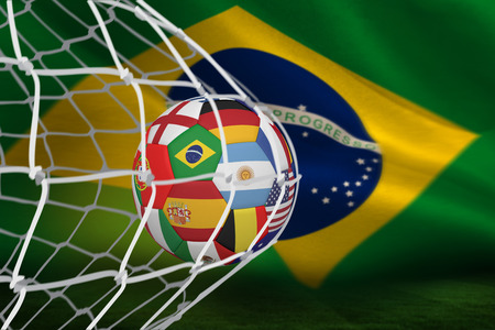 Football in multi national colours at back of net against brazilian flag waving photo