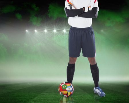 Composite image of goalkeeper standing with international ball against football pitch under green sky photo