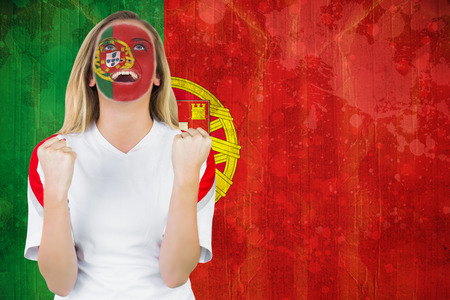 Excited portugal fan in face paint cheering against portugal flag in grunge effect photo