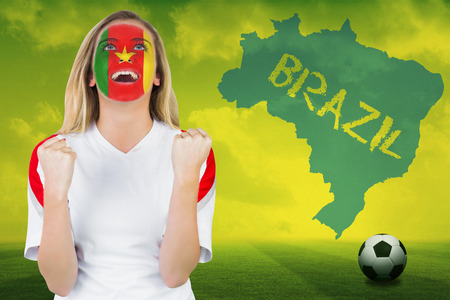 Excited cameroon fan in face paint cheering against football pitch with brazil outline and text photo