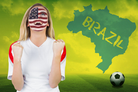 Excited fan in usa face paint cheering against football pitch with brazil outline and text photo