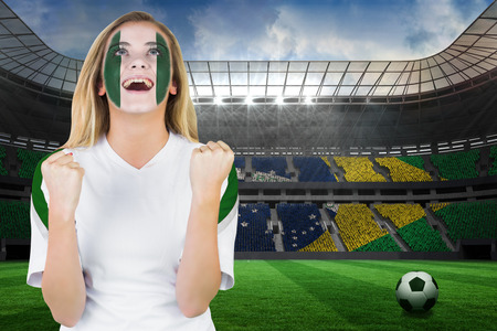 Excited nigeria fan in face paint cheering against large football stadium with brasilian fans photo