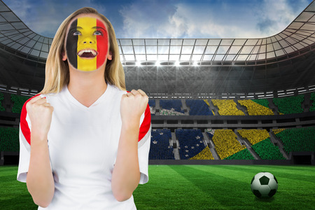 Excited belgium fan in face paint cheering against large football stadium with brasilian fans photo