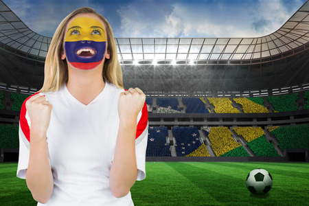 Excited colombia fan in face paint cheering against large football stadium with brasilian fans Stock Photo