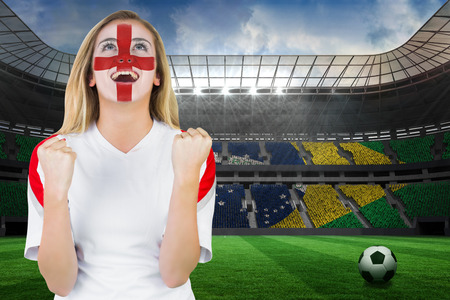 Excited fan england in face paint cheering against large football stadium with brasilian fans photo