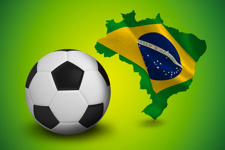 Black and white football against green brazil outline with flag photo