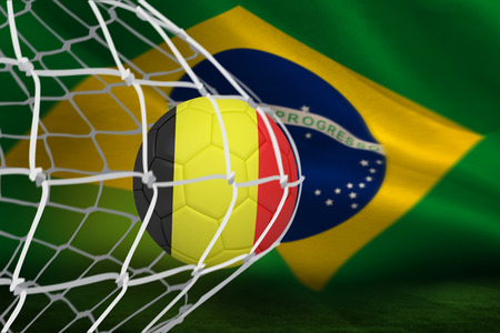 Football in germany colours at back of net against brazilian flag waving photo