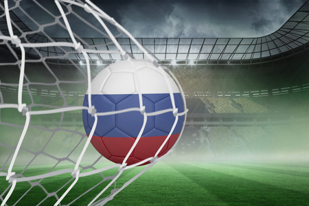 Football in russia colours at back of net against misty football stadium under spotlights photo