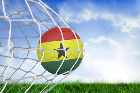 Football in ghana colours at back of net against field of grass under blue sky photo