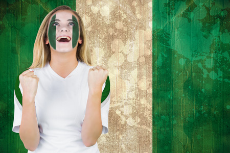 Excited nigeria fan in face paint cheering against nigeria flag in grunge effect photo
