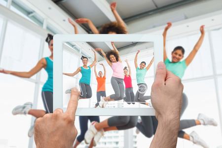 Hand holding tablet pc showing fitness class and instructor jumping in fitness studio photo