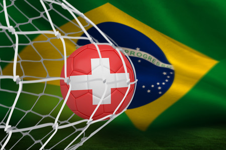 Football in swiss colours at back of net against brazilian flag waving photo