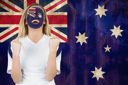 Excited australia fan in face paint cheering against australia flag in grunge effect photo