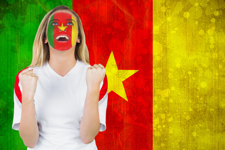 Excited cameroon fan in face paint cheering against cameroon flag in grunge effect photo
