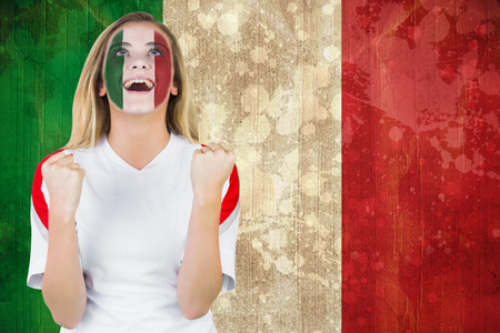 Excited italy fan in face paint cheering against italy flag in grunge effect photo